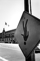 An upside down street sign at Mexico City's center.  In the background is the National Palace. Mexico City