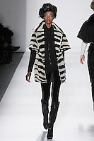 Model walks runway in a black+ivory clarence house silk velvet zebra mini storm coat, black handloomed cashere/silk zipped ribbed turtleneck+velvet leggings, from the Zang Toi Fall 2012 &quot;Glamour At Gstaad&quot; collection, during Mercedes-Benz Fashion Week New York Fall 2012 at Lincoln Center.