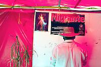 Messico Nogales Confine Arizona Messico Migranti   tende di accoglienza dei clandestini rispediti in Messico dalla polizia statunitense. Messicano di spalle di fronte a manifesto sui migranti e immagine di Gesu'<br /> Mexico Nogales Arizona Mexico Border Migrants tents for the reception of illegal immigrants sent back to Mexico by US police . Mexican shoulders in front of manifesto on migrants and image of Jesus '