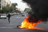 A Mousavi supporter runs past a fire on Khosh Street, pursued by Basij (Basiji) militia and Revolutionary Guards. Following a disputed election result, thousands of supporters of opposition candidate Mir-Hossein Mousavi took to the streets in protest.