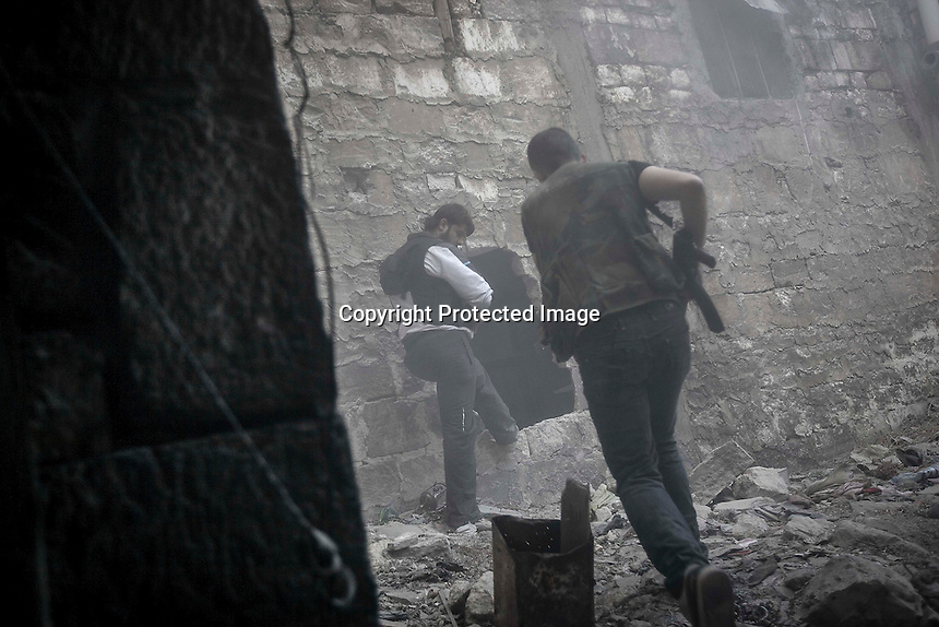In this Saturday, Nov. 03, 2012 photo, rebel fighters move through an explosion smoke as they repel a coordinated attack by mortar, tank and aerial artillery carried out by loyalists to President Bashar Al-Assad during heavy clashes in the nearby Castel Harami battlefield in the Jdeide district of Aleppo, the Syrian's largest city. (AP Photo/Narciso Contreras).