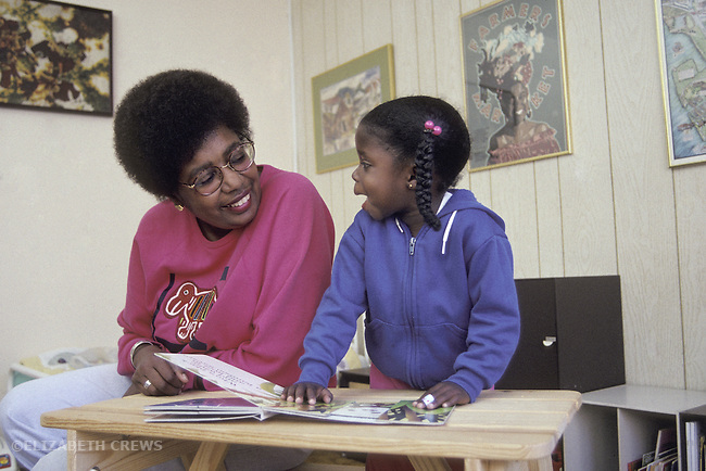 Berkeley, CA African American grandmother and granddaughter, three years old, in animated conversation about book
