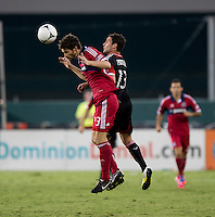 Chris Pontius (13) of D.C. United goes up for a header with Gonzalo Segares (13) of the Chicago Fire at RFK Stadium in Washington, DC.  D.C. United defeated the Chicago Fire, 4-2.