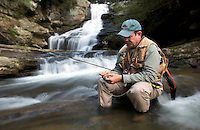 A fly fisherman sits on a rock in a trout stream and ties a fly onto his line below a waterfall in North Carolina.