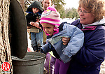 WOODBURY, CT, 05 MARCH 2011-030511JS08--FOR COUNTRY LIFE-Chris Harrison of Natuatuck, right, holds up her niece Cailynn Connolly, 4, of Cheshire, so she can get a look at how much tree sap has been collected during a maple sugar demonstration at the Flanders Nature Center in Woodbury on Saturday. The center will hold its Flanders' famous finale maple celebration on Saturday March 19, 2011 from noon to 4 pm at the Sugar House. <br /> Jim Shannon/Republican-American