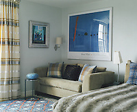 The intense blue of a poster by Miro seems to light this bedroom with its interesting mix of textures and fabrics