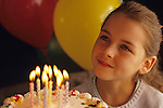 Colorful balloons with 9 (nine) year old girl celebrating a birthday with cake and candles, warm light on smiling face.