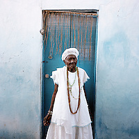 105 year old Mai Filinha, the Perpetual Judge (eldest member) of the Irmandade da Boa Morte (Sisterhood of the Good Death). The Sisterhood began as a bank in 1823, founded by freed slaves, to finance the freedom of men, women and children still bonded by slavery. The community, which is still made up of the descendents of slaves, is one of the oldest and most respected worship groups for Candomble, the major African-based religion in Brazil. The sisterhood practices a syncretised worship that combines Candomble, Catholicism and Islamic elements. Thanks to their microcredit scheme, and the two hundred religious events they organise throughout the year, the Sisterhood have achieved a central role in regional society, preserving some of the traditional African values that slavery brought to Brazil.