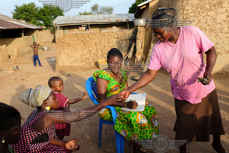Anita Sutha (seated in green), a junior high school teacher by profession, also coordinates a number of women's groups in her area.  She is seen with members of a 'susu' group - an informal savings and loan club - that she coordinates in her home village of Gbengbee.