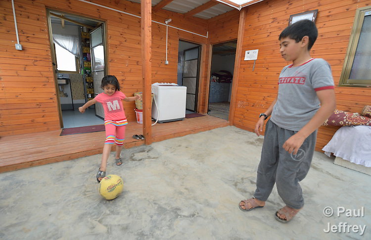 Raghad Jame'a, 7, and her 12-year old brother Ahmad play football in the courtyard of their family's transitional house built for them by Catholic Relief Services in Khan Yunis, Gaza. Houses in the area were destroyed by the Israeli military during the 2014 war between the state of Israel and the Hamas government of Gaza. CRS is building hundreds of transitional homes where families can live for several years until they can rebuild their own permanent home.
