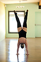 A heavy athletic woman performing a beautiful handstand.