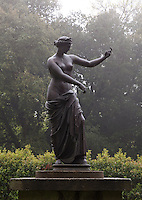 A draped classical figure beckons to visitors in the gardens at Killruddery