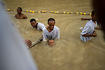 Orthodox-Christian pilgrims of Eritrean and Ethiopian descent, living as migrants in Tel Aviv, Israel, baptise during Epiphany holiday, at the baptismal site of Qasr el-Yahud on the Jordan River, near the West Bank town of Jericho. The site is believed to be where Jesus was baptised by John the Baptist.