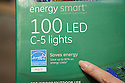 Finger pointing at saves energy sign on sustainable holiday lights package. General Electric brand 'Energy Smart' energy efficient LED holiday lights at Cosco. San Francisco, California, USA