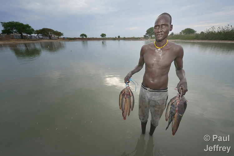Mobil Kon displays fish he caught in Poktap, a town in South Sudan's Jonglei State where conflict, drought and inflation have caused severe food insecurity. The Lutheran World Federation, a member of the ACT Alliance, is helping families tackle food problems, including by providing cash for the purchase of fishing line and hooks.