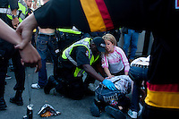 A woman speaks to an officer over a man who was severly injured during a riot on the downtown streets of Vancouver,BC after the Canucks were defeated by the Boston Bruins in the Stanly Cup on June 15, 2011. (photo copyright Karen Ducey)