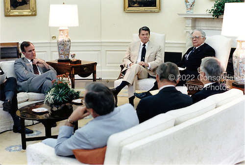 United States President Ronald Reagan meets in the Oval Office with members of the Foreign Intelligence Advisory Board on Tuesday, July 14, 1987.  Seated, clockwise, from left, are: U.S. Vice President George H.W. Bush, President Reagan, Leo Cherne, James Wilson, John Foster, and White House Chief of Staff Howard Baker.Meeting .Mandatory Credit: Pete Souza - White House via CNP