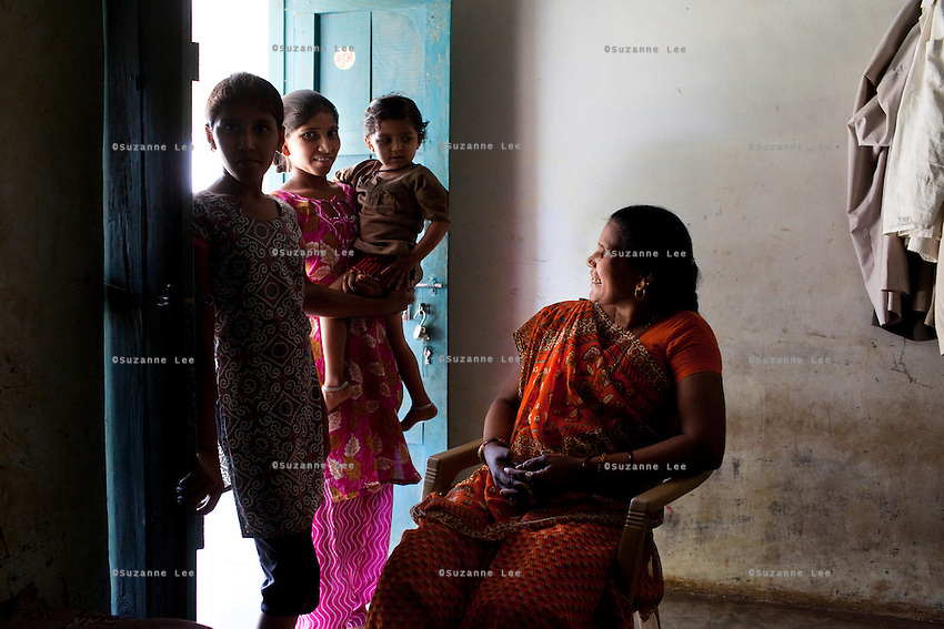 "Shardaben's eldest daughter, Lakshmi (18, in pink) carries a younger relative as Shardaben looks on. 200,000 rupees out of the money Shardaben earned from surrogacy will soon be given to Lakshmi's husband-to-be as her dowry. ..Shardaben Kantiben, 31; Husband is Kantibhai Motibhai (37).3 children --- 2 girls -  Usha(15) and Lakshmi (18, in pink); 1 boy, Chintan (17).- Education costs for all three come to Rs. 15,000 per year.- Shardaben was a two-time surrogate. First time she gave birth to twin girls for a Taiwanese couple and the second time a boy for an Indian couple from America (photo on TV set because she's proud that it was a boy).- The second time she became emotional and they got a gold ring of Rs. 1,500 made for the boy, which they presented to the biological parents. They are not in touch with either couple..- From the two surrogacies, they earned a little over 700,000rupees..-200,000rupees will be given as dowry for Lakshmi's wedding..- They leased agricultural land (Rs. 2 lakhs for five years) which earns them Rs. 60,000-70,000 a year; they bought two buffaloes worth Rs. 60,000 and make almost 6000-7000 per month selling milk; they bought a motorbike for Rs. 25,000; they put some money into house repairs and the construction of toilets, and opened a fixed deposit in Shardaben's name for Rs. 1.5 lakh and one in the name of their son, Chintan, for Rs. 25,000..Quotes..""Everyone says they'll keep in touch and take down addresses and phone numbers but nobody looks back. And I guess it works well. Our main interest was in the money. Their main interest is in the baby."" - KantiBhai.""Their rules apply at the surrogate house. It does curtail the freedom. When I used to go, everybody would just be lying. They count the days when they can go back."" - Kantibhai.""Ours is natural birth but surrogacy is a man-made pregnancy. There's a lot of risk. She must have taken at least 300 injections."" - Kantibhai of his wife...The Akanksha Infertility Clinic is known internatio"