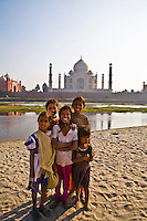 Smiling children  standing on the bank of river Yamuna and Taj Mahal in the background.<br /> (Photo by Matt Considine - Images of Asia Collection)