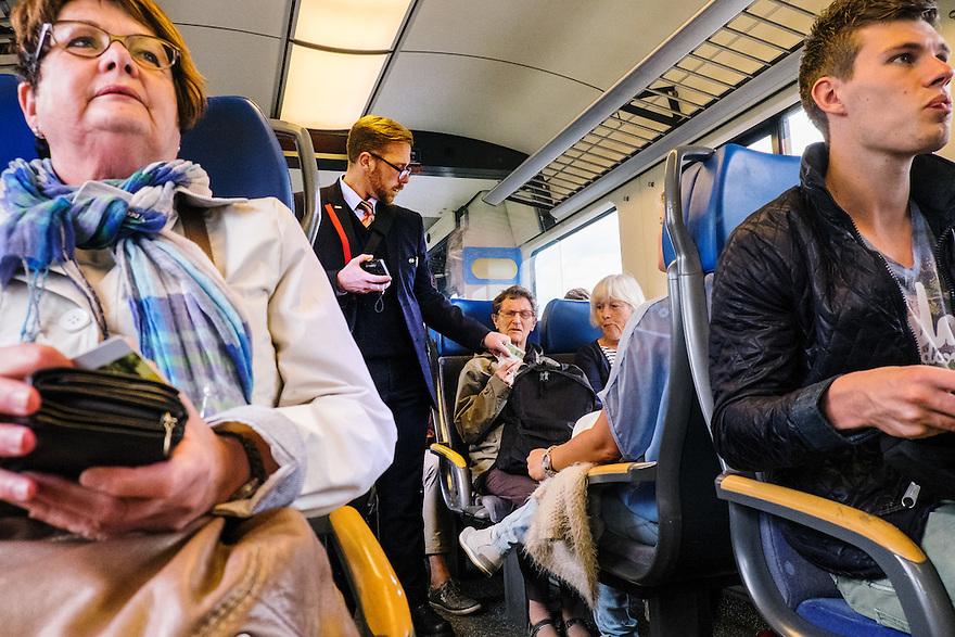 Nederland, Utrecht, 16 juni 2015 <br /> Conducteur controleert kaartjes in de trein.<br /> <br />  Foto: Michiel Wijnbergh
