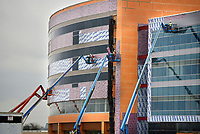NWA Democrat Gazette/SPENCER TIREY A line of construction workers in bucket lifts dot the front of the newly constructed Children's Hospital, Friday, March 17, 2017 in Springdale as they work to finish the exterior. The hospital is expected to open in early 2018.