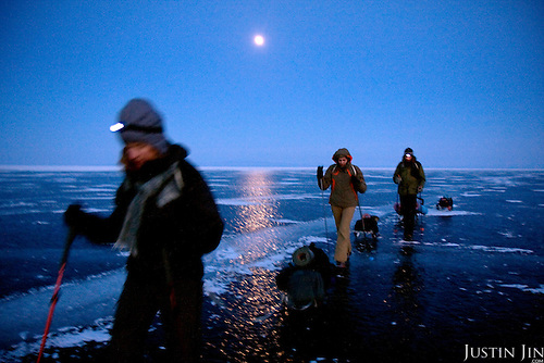 (Left to Right) Heleen, Nastya and Misha trek across frozen Lake Baikal in Siberia, Russia, under the moonlight.  (second night)..They are a group of five people: Justin Jin (Chinese-British), Heleen van Geest (Dutch), Nastya and Misha Martynov (Russian) and their Russian guide Arkady. .They pulled their sledges 80 km across the world's deepest lake, taking a break on Olkhon Island. They slept two nights on the ice in -15c. .Baikal, the world's largest lake by volume, contains one-fifth of the earth's fresh water and plunges to a depth of 1,637 metres..The lake is frozen from November to April, allowing people to cross by cars and lorries.