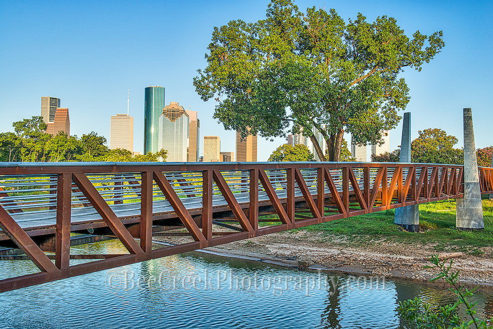 This is a pedestrian bridge over the Buffalo Bayou near downtown Houston with many of  the city's skyscrapers in the view.  You can see the iconic Chase Towers, the Heritage Plaza, and many other of the tall buildings in downtown area.