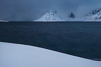 Mountain vanish into approaching winter storm, Reinefjord, Moskenesøy, Lofoten Islands, Norway