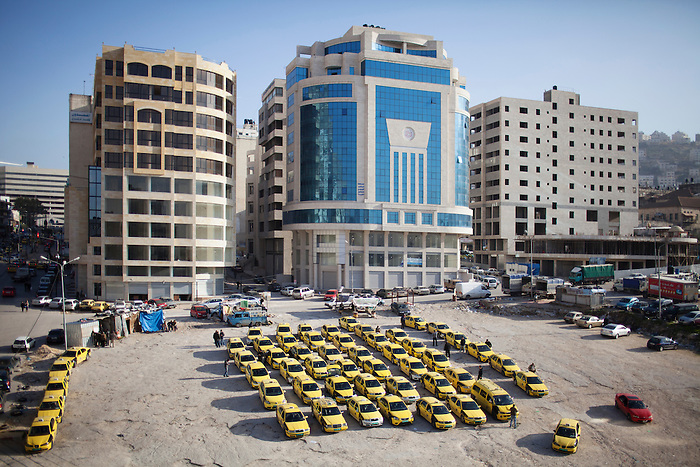 """Jan 2013, Nablus. In the second biggest city in West Bank, real estate and new offices are flourishing.  In the Rafida quarter, the Paltel group has just built an office building on the """"taxi square"""" . The economical boom has accelerated since the blockade on the city by the Israeli army was removed in 2009. Before then, Nablus people needed a permit for going out of the city. However, movement is still limited with the presence of the 58 Israeli checkpoints inside  the West bank, in addition to the restrictions of access to Jerusalem and Gaza, still affecting heavily the economical development in Palestine."""