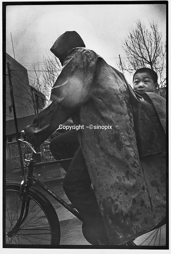 A father and son exposed to the elements ride through Beijing streets...PHOTO BY WANG TONG / SINOPIX