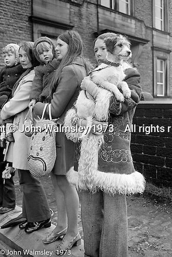 """Watching the """"Nutters' Dance"""", Bacup, Lancashire  1973.  The """"Nutters' Dance"""", Bacup, Lancashire  1973.  On Easter Saturday every year the """"Coco-nut"""" dancers gather at one boundary of the town and dance their way across to the other accompanied by members of the Stackstead Silver Band, collecting for charity as they go.  It includes a short stop in one of the pubs."""