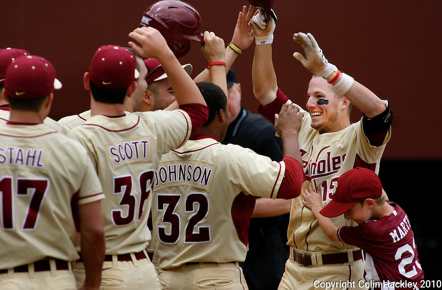 TALLAHASSEE, FL 3/28/10-FSU-MARY BASE10 CH05-Florida State's Tyler Holt (15) right, celebrates at the plate with teammates after he homered in the fifth inning against Maryland Sunday at the Dick Howser Stadium in Tallahassee. The home run was Holt's final step in hitting a cycle in order. Holt was the first Seminole since Stephen Drew to perform such a feat. Drew hit for the cycle against Wake Forest in 2004. The Seminoles beat the Terrapins 9-5. ..COLIN HACKLEY PHOTO