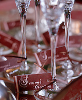 Season Greetings cards are tied with a ribbon to the base of each champagne flute