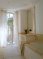A light, contemporary bathroom has French windows opening onto the garden