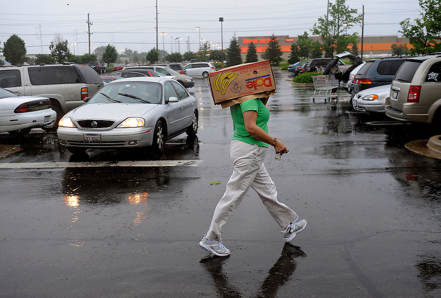 Jonathan Miano/Staff Photographer/Naperville.20100618 Naperville ..Lucia Robles of Plainfield shields herself from the rain with a box in the Costco parking as a thunderstorm passes over Naperville Friday afternoon.