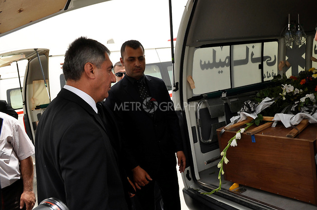 SULAIYMANIYAH, IRAQ:  Sulaimaniyah Governor, Bahroz Hama Salh, places flowers on the caskets of those killed in a fire at the Soma Hotel.<br /> <br /> On July 15, 2010 a fire in the Soma Hotel killed around 40 people including women, children and internationals from the US, Britain, Canada, Australia, Venezuela, Lebanon, South Africa, Bangladesh, the Philippines, Sri Lanka, and Cambodia..Photo by Aram Karim/ Metrography