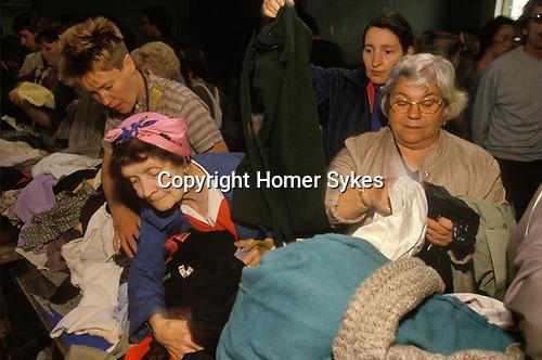 Woman wearing Mrs Mop charwoman style head scarf Jumble sale Dulwich South London England