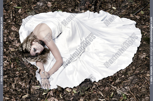 Stock photo of a Young beautiful bride in a white wedding dress lying on fallen autumn leaves Emotional artistic conceptual photo Horizontal