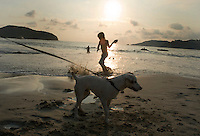 Lucas play's in the sunset with Coco the dog in the foreground. photo shoot in Zihua with Federico Rigoletti and family, Diego Garcia and his daughters, and the Wiseman family as part of the Puntarena cook book