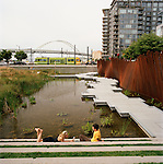 A couple enjoying the afternoon at Tanner Springs Park in Northwest Portland, Oregon's Pearl District.  The Fremont Bridge and a streetcar are visible in the background.  What is now known as the Pearl District was once a wetland and lake fed by streams that flowed down from the nearby hills in southwest Portland. These wooded hillsides provided a natural filter for the streams, cleansing the water as it made its way to the Willamette River. The springs from Tanner Creek, named for the tannery built by pioneer Daniel Lownsdale in the 1860s, flowed into the shallow basin of Couch Lake, now the area surrounding Tanner Springs Park. As the population of Portland grew in the late 19th century, Tanner Creek was rerouted through an underground system of pipes to the Willamette River. The lake and the surrounding wetland were eventually filled to make way for warehouses and rail yards which in turn were replaced by residences, shops, and public spaces. Today, the park sits about 20 feet above the former lake surface.