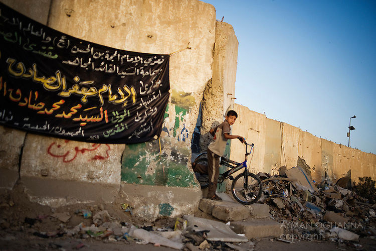 ..A boy emerges through a passageway cracked through one of the columns of blast walls that line Sadr City a sprawling Baghdad slum home to three million people and bastion of the fearsome Mahdi army, a militia loyal to the fiery cleric Moktada al-Sadr. ...Ayman Oghanna for The New York Times