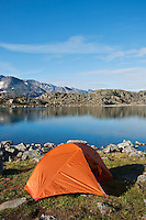 Backpacking tent camp on shore of lake Blørnbøljønne on Besseggen trail, Jotunheimen national park, Norway