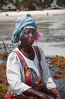 Jambiani, Zanzibar, Tanzania.  Woman at her seaweed plot.  She has come to harvest seaweed, to export to Asian markets.  This work can only be done at low tide.