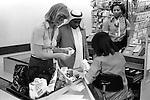 .Arabs London UK 1977. Middle Eastern people came to Britain for subsidised health care in Harley Street clinics. . They mainly stayed in cheap hotels in Earls Court. Arab man Earls Court supermarket  two check out women help him with shopping and paying the bill.