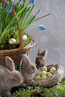 Detail of an Easter still life with toy bunny rabbits around a nest filled with small chocolate eggs and a wicker basket of grape hyacinths