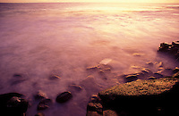 Long exposure with ocean washing up on rocks at sunset