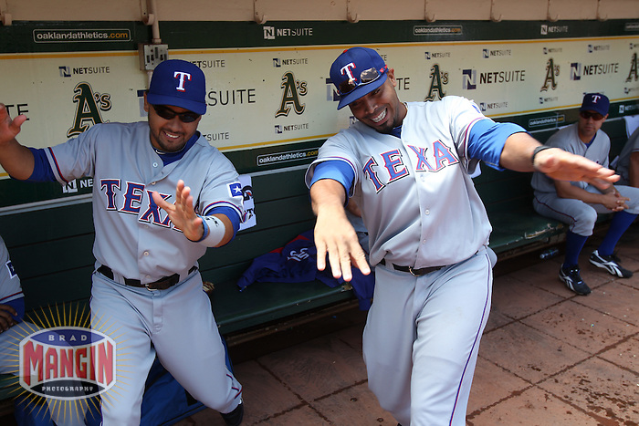OAKLAND, CA - AUGUST 8:  Andres Blanco #3 and Nelson Cruz #17 of the Texas Rangers get ready in the dugout by doing a handshake before the game against the Oakland Athletics at the Oakland-Alameda County Coliseum on August 8, 2010 in Oakland, California. Photo by Brad Mangin