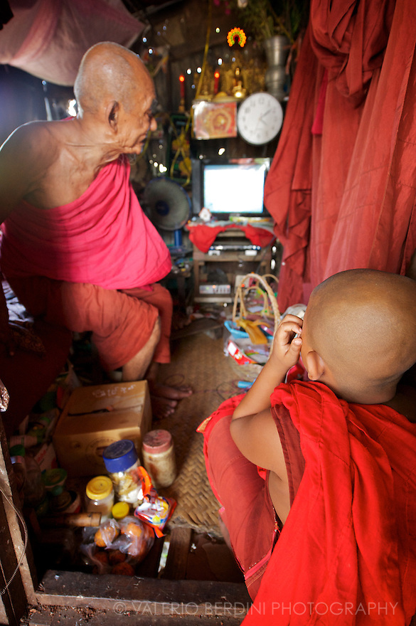 An old monk and a young samanera watch an old television together. Monks have traditionally taught reading and writing to young girls and boys, and morals, philosophy and meditation to older students.