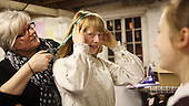 """Hair dresser working on the actors.  Drama group for 8-13s rehearsing a production of """"Alice"""" in the Mill Studio at the Yvonne Arnaud Theatre, Guildford, Surrey."""