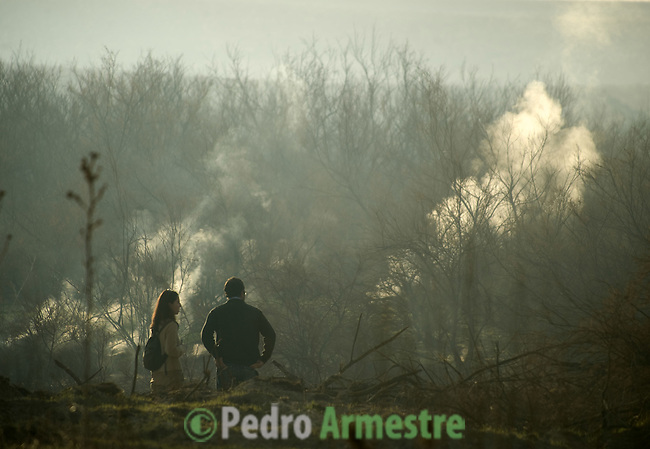 Two residents watch white smoke of a fire underground in the national park of Las Tablas de Daimiel, in Ciudad Real on November 16, 2009. The European Union launched an investigation into Spanish wetland that has turned bone dry through mismanagement of water resources  from areas where fish once swam. The EU wants the Spanish government to explain how it plans to save Las Tablas de Daimiel National Park.The park, one of Spain's few wetlands, is classified as a UNESCO biosphere site and an EU-protected area because of its birdlife. But it has been drying up for decades, largely because of wells dug by farmers on the edges of the park to tap an aquifer that feeds the wetland's lagoons. Many of the wells are illegal. Environmentalists call this case a particularly glaring example of how a natural resource can be abused. (c)Pedro ARMESTRE